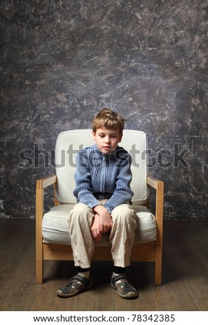 little boy sitting on white chair in studio of photographer, brown background