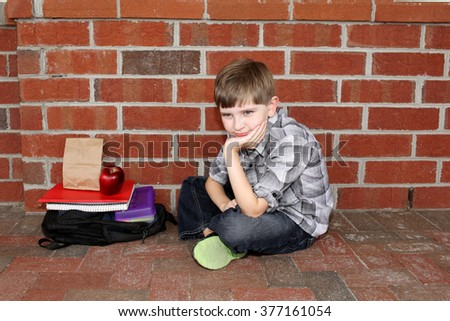 Little boy sitting outside of school with lunch and school books. - stock photo