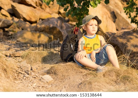 Little boy sitting resting on the ground amongst rocks with his rucksack behind his back as he takes a breaks while hiking in the wilderness - stock photo