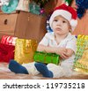 Little boy sitting with  Christmas gift at home - stock photo