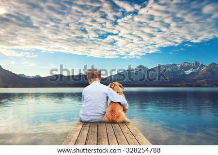 little boy sitting with his dog on the shore of Lake, child hugging his dog - stock photo