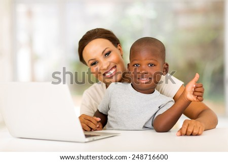 little boy sitting with his mother giving thumb up - stock photo