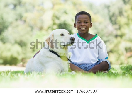 Little boy sitting with his pet labrador in the park on a sunny day