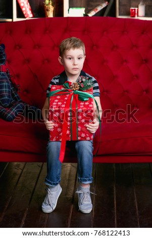 Little boy sitting with the teddy bear on the red coach with christmas present in his hands