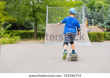 Little boy skating towards a ramp at a skate park on his skateboard as he enjoys a hot summer day out in the fresh air - stock photo