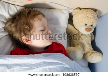 Little boy sleeping in his bed