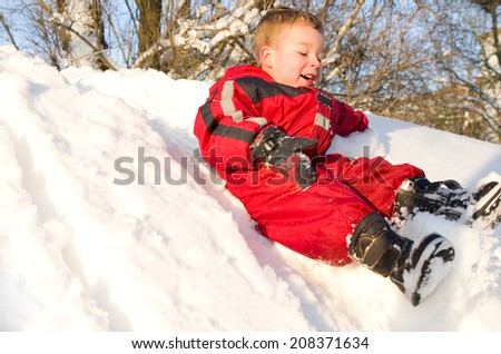 little boy sliding down a snow mountain - stock photo