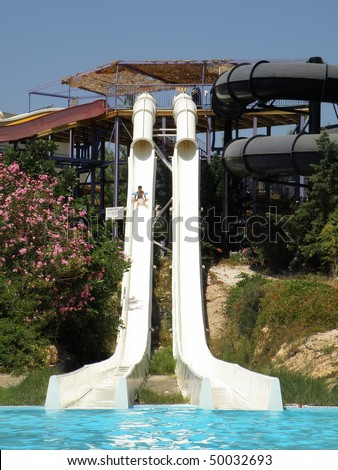 little boy sliding down big kamikaze water slide - stock photo