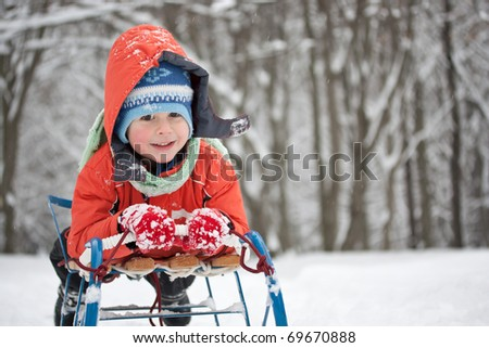 Little boy sliding in the snow