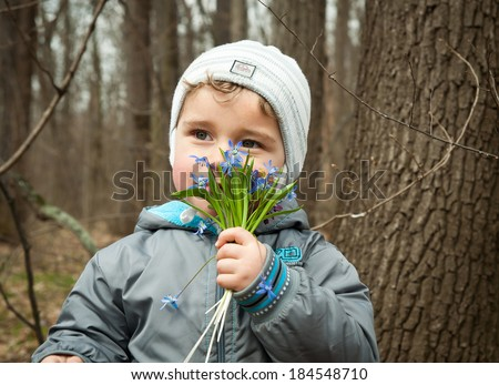 little boy smelling the aroma of snowdrops in the forest - stock photo