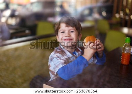 Little boy smile with hamburger in fast food restaurant behind glass - stock photo