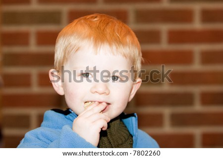 Little boy smiling and eating a potato chip
