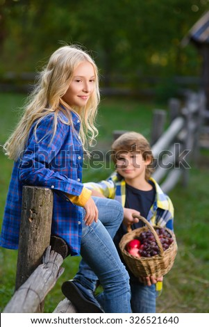 little boy smiling and girl on fence looking at each other in the autumn Park - stock photo