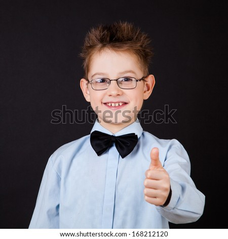 little boy smiling and showing ok sign over the black
