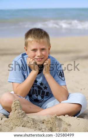 Little boy smiling sitting on the beach near the sea