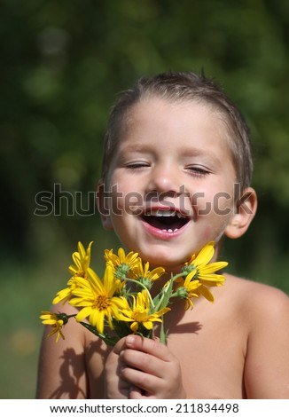 Little boy smiling with flowers - stock photo