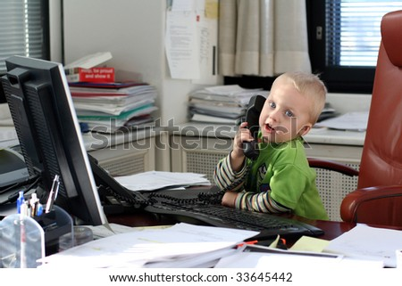 Little boy speaking on phone in the office - stock photo