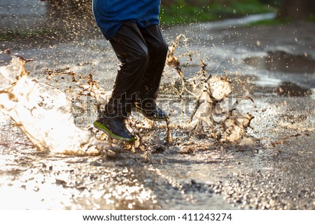 Little boy splashing in a mud puddle, jumping into a puddle