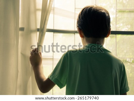 Little boy standing behind the window vintage  - stock photo