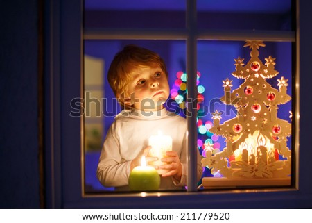 Little boy standing by window at Christmas time and holding candle. With colorful lights from Christmas tree on background, selective focus. - stock photo