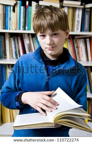 Little boy  standing near the bookshelf - stock photo