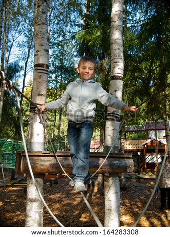 Little boy standing on a tightrope - stock photo