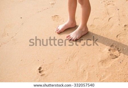 Little boy standing on the beach sand alone