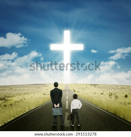 Little boy standing on the road with a businessman and looking at a cross on the end of the road - stock photo