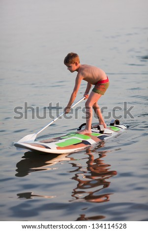 Little boy standing on  the windsurfing board with paddle. Evening light - stock photo