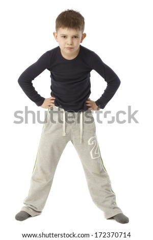 Little boy standing straddle with hands on hip, looking strict. Full size. - stock photo