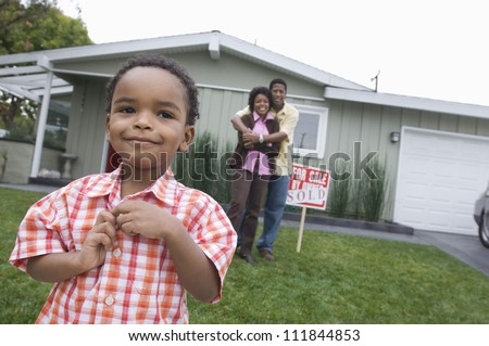 Little boy standing with his parents embracing in front of the house