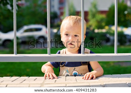 Little boy stands behind the fence and looks into the distance