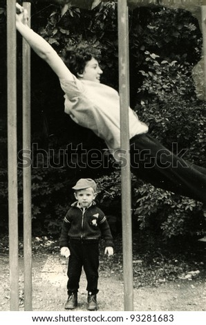 little boy stands near the horizontal bar, which swings teenager, Kursk, USSR, 1984 (very grainy image)