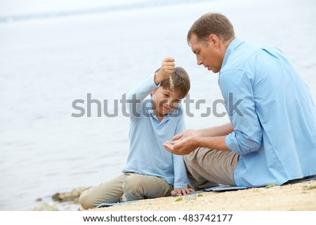 Little boy strewing sand into his fathers hands