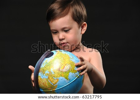 Little boy studying a globe against black background