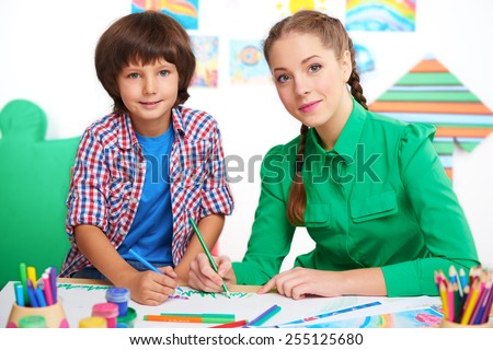 Little boy studying with young teacher in a preschool center for children. Teacher drawing picture with boy and looking at camera - stock photo