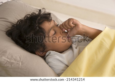 little boy sucking his thumb at night - stock photo