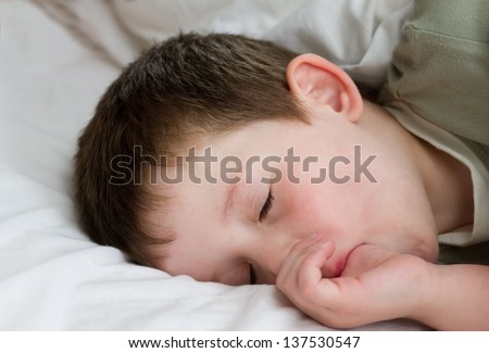 little boy sucking his thumb whilst asleep