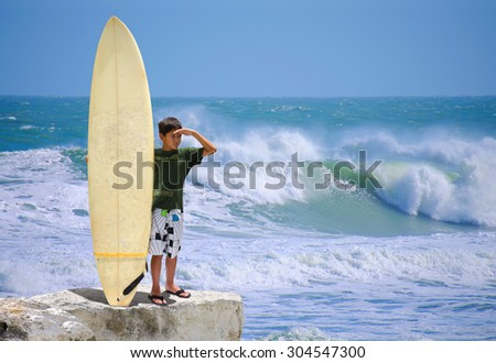 Little boy surfer with his surfboard at the beach on a rocky shoreline checking out the big waves getting ready to go surfing. - stock photo