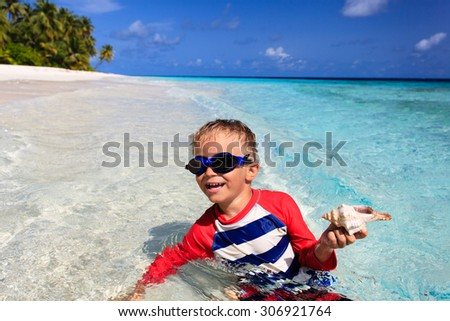 little boy swimming holding shell on tropical beach