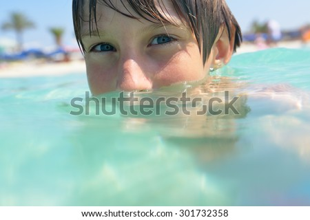 little boy swimming in sea with clean turquoise water transparent - stock photo