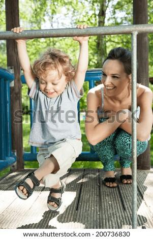 Little boy swinging on monkey bars on playground - stock photo