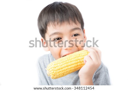Little boy taking corn and eating on white background - stock photo