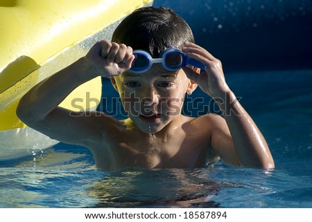 Little boy taking his goggles off in the swimming pool - stock photo