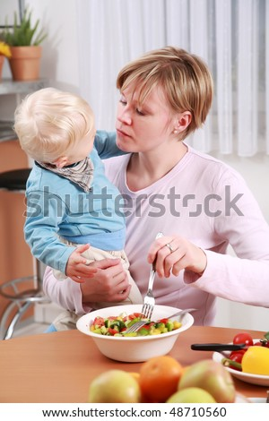 Little boy tasting vegetable salad with his mother - stock photo