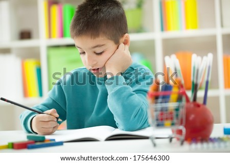 little boy teaches and writes something in a notebook