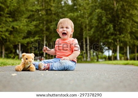 Little boy the kid in blue jeans crying bitterly, sitting on the ground next to a soft toy in the summer - stock photo