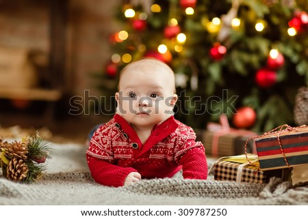 Little boy the kid in the red sweater lying on a cozy blanket on the Christmas tree and garlands in the house next to the gifts - stock photo