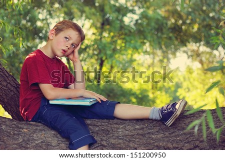 Little boy thinking about what he read - stock photo