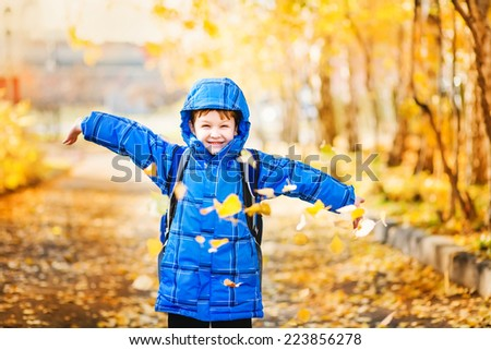 Little boy throws the autumn leaves in the air. Instagram filter. - stock photo